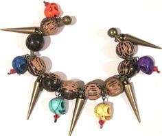 This fun and unique bangle bracelet is handcrafted from antique brass tone wire & fasteners, wood beads, stone skull beads, acrylic spikes.  #jewelry #bracelet #halloween #skull #spikes #ariwolfchild #bangle