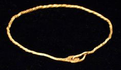 "694   ROMAN GOLD BRACELET          II-III c. A.D. Solid round hoop with rectangular cross section, spirally twisted; hammered flat at one end with a round opening, other end tapered and forming a hook. 2.5""x 2.5""(6.4 x 6.3 cm). $ 850"