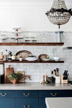 Navy cabinets, concrete counters, open reclaimed wood shelving, basketweave marble backsplash                                                                                                                                                                                 More