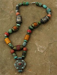 "Necklace | Nan Stine.  Contemporary Tibetan Ghau amulet decorated with turquoise and coral,  two silver and copper Tibetan prayer wheels, two old amazonite beads, two Bakelite ""amber"" beads, glass, turquoise and carnelian"