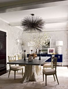 A Jean de Merry light fixture hangs above a dining table by the Groundwork Group and 18th-century Italian chairs; the mirror is vintage, the cabinet is by Tommi Parzinger, and the hand-painted wallpaper and cowhide rug are from Stark. Photography by Eric Piasecki - ELLEDecor.com