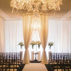 Such an elegant ceremony setting, with gold chandeliers, floor length curtains, and black chairs