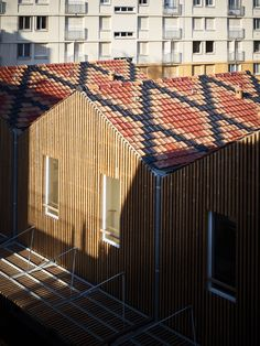 French firm Odile Guzy Architectes has completed a social housing project in the city of Chalon-sur-Saône, comprising a row of terraced houses and an adjacent apartment block with timber facades that extend to form slatted solar screens.