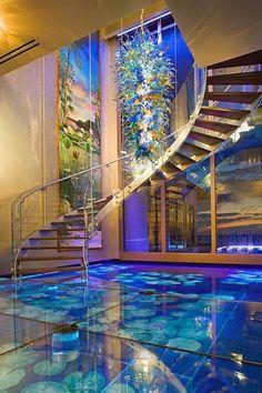 Escalera curva interior y espejo de agua con juego de luces...