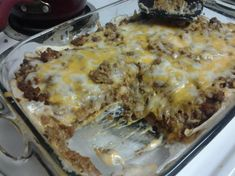 Creamy Burrito Casserole  1 lb ground beef or 1 lb ground turkey  1/2 medium yellow onion, chopped  1 (1 1/4 ounce) package taco seasoning  6 large flour tortillas  1 (16 ounce) can refried beans  2 -3 cups shredded taco cheese or 2 -3 cups cheddar cheese  1 (10 3/4 ounce) can cream of mushroom soup  4 ounces sour cream  jarred hot sauce, if desired to spice it up
