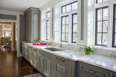 Beautiful kitchen boasts gray raised panel cabinets paired with white marble countertops and backsplash.