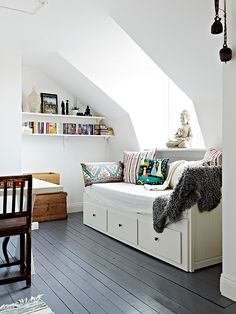 A day bed or captain's bed with throw pillows can turn a spare room into a sanctuary for quiet reading.