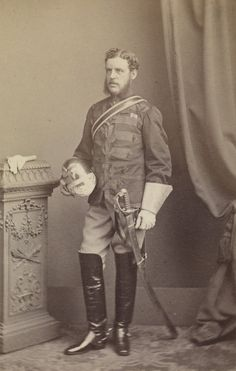 Photograph of Major William Reynolds. He is standing facing partly left holding a helmet in his right hand. He is wearing military uniform and riding boats and there is a sword by his side. There is a pair of gloves on the wooden pillar to the left and a curtain draped to the right. Major William Reynolds commanded the 3rd Scinde Horse Regiment during the Second Anglo-Afghan War. He was killed at Khushk-e-Nakhud in Feburary 1879.