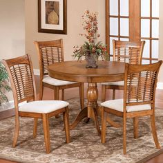 Sturdy hardwood the Pedestal 5 Piece Round Dining Set features a warm and inviting oak finish. The stylish chair seats are upholstered with plush cream fabric.