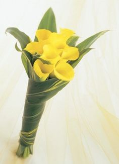 I love how the leaves wrap around the flowers. natural, simple and elegant. All yellow calla lilies bouquet.
