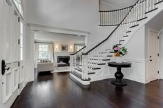 This entry way!!! love the wainscoting and perfect table to nestle into the curve of the staircase.