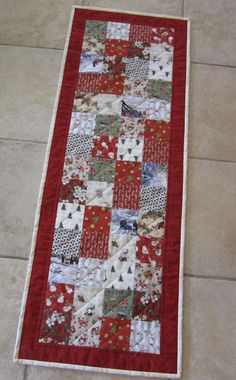 Decorate your Christmas table with this fun Christmas table runner! The patchwork pieces include themes like birds, candy canes, snowmen, Santa Clauses, holly leaves, toys and other Christmas decor in predominantly red and green tones. A frame of red fabric surrounds all the happy