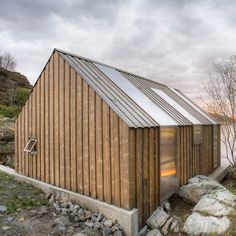 Strips of glazing wrap the walls and roof of a timber waterside summerhouse in Aure, Norway.: