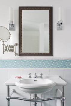 White and turquoise bathroom features metal mirror flanked by milk glass sconces paired with wall-mounted accordion shaving mirror over St Thomas Creations Nouveau Console Bathroom Sink positioned against wall clad in turquoise diamond pattern tiled backsplash above stacked white grid tiles.