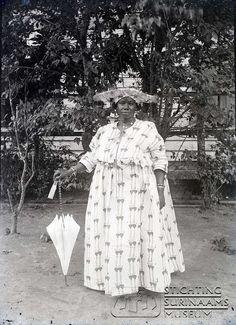 Kotomisi met parasol. Datum: rond 1915 Locatie: Paramaribo, Suriname Vervaardiger: Augusta Curiel Inv. Nr.: gn-04-81 Fotoarchief Stichting Surinaams Museum