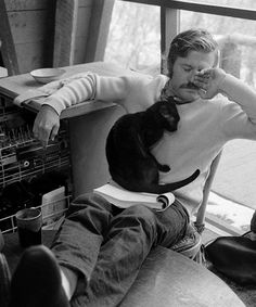 Robert Redford and the family's cat take a break from reading a script (1969)