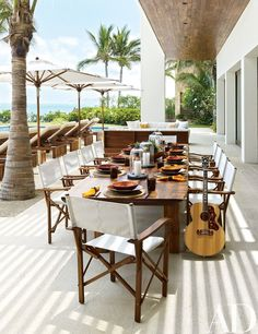 On Crawford and Gerber's pool terrace, Christian Liaigre director's chairs surround a custom-made dining table; the Gibson guitar was a gift from Kid Rock, a frequent guest.