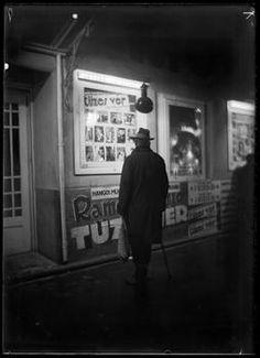 Szerző:Kinszki Imre (1901-1945) Cím:[Este, férfi egy mozi kivilágított kirakata előtt] [Fénykép] Dátum:1931 Budapest, Arch, Fictional Characters, Longbow, Arches, Fantasy Characters, Wedding Arches, Bow, Belt