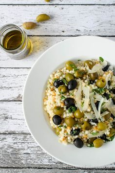1 cup tri color couscous  2 garlic cloves, mashed  1 teaspoon salt  2 tablespoons freshly squeezed lemon juice  1 teaspoon Dijon mustard  2 teaspoons white balsamic vinegar  3 tablespoons extra virgin olive oil  freshly ground black pepper  1 1/3 cups black olives  1 1/3 cups green olives  1/4 cup finely diced red onion  1/2 cup cilantro or flat leaf parsley, minced  2-3 tablespoons minced mint  1/4 cup shaved Parmesan cheese