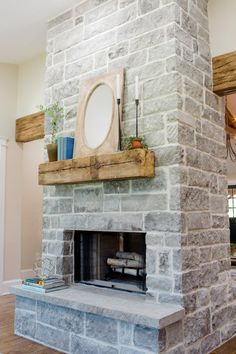 HGTV's Fixer Upper invites you to take a look at this remodeled living room with a gray stone fireplace and reclaimed wood mantel. Grey Stone Fireplace, Fireplace Design, Fireplace Ideas, Fireplace Makeovers, Basement Fireplace, Ethanol Fireplace, Fireplace Mantles, Fireplace Decorations, Stone Fireplaces