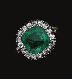 EMERALD AND DIAMOND RING, EARLY 19TH CENTURY    Centring on a cushion-shaped emerald bordered by single-cut diamonds, to a closed back mount