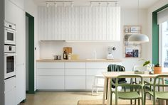 A white kitchen with green accents. Sleek white VOXTORP cabinet doors can be seen on the lower section and 3-dimensional HERRESTAD cabinet doors on the upper section. An LISABO table in ash veneer and YPPERLIG chairs in green can be seen in the foreground.