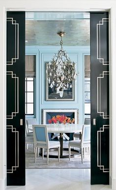 the chandelier is the star in this dining room.  i like that walls and trim are painted blue.  metallic ceiling.  black & white pocket doors.