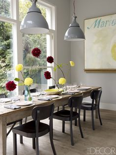London-based cosmetics executive Christine d'Ornano uses the dining area of her kitchen—part of a minimalist glass-walled addition overlooking the garden of her Victorian home in Notting Hill—for small, casual meals. The vintage pendant lamps are from England's Rover car factory.   - ELLEDecor.com