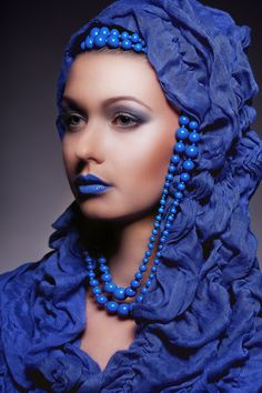 Model dressed in blue and wearing blue pearls
