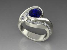 Custom made wedding ring with a natural sapphire and 1.26 ct round 0.2pt diamonds. Can be found at Moses Jewelers in San Antonio, Texas.