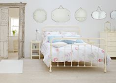 Make a beautiful display with vintage mirrors and an iron bed