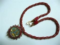 """A vintage Czech button serves as a focal point, surrounded by Japanese seed beads and Czech crystals.  The button is heavily embellished with Czech crystal beads on the back side and may be worn with either side facing up for a beautiful, versatile piece. Attached to a Ndebele rope of red and gold Delica beads and finished with hand-beaded caps and an S shape closure.  This delightful necklace measures 18"""" long; focal point is 1 1/2"""" wide."""