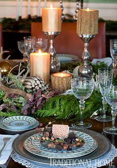 """Pottery Barn chargers and mercury glass candle holders mix confidently with Bernardaud's """"Constance"""" porcelain plates. Christmas greens on the dining table add extra holiday flair."""