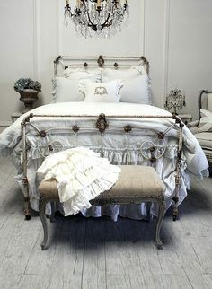 rusty bed. white and very pale pastel bed linens. crystal chandelier.