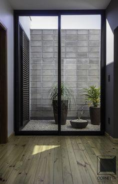 Pequenos detalhes fazem a diferença: hall de entrada com ventilação cruzada e jardim externo. Destaque para alvenaria em bloco aparente e piso em assoalho de pinus de reflorestamento.