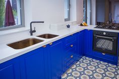 Kitchen design in Bucharest, pattern tiles, blue furniture and copper accents. Cool copper sink.