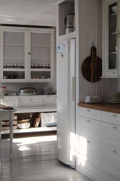 I love the white floors, the open lower shelves. And the curtain behind the glass doors.