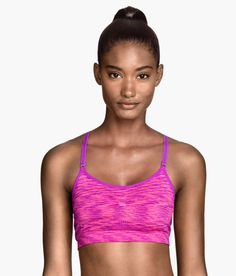 Bright magenta sports bra with lightly padded cups, removable inserts, and narrow adjustable straps. | H&M Sport