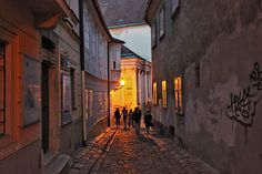 Golden light from lanterns washes over a typical cobblestone street in Bratislava Slovakia
