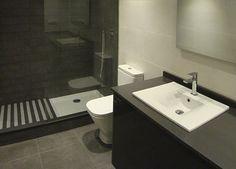 Foto de reforma de baño moderno en tonos blanco, gris perla y antracita con mueble de baño gris encimera silestone antacita y box ducha con mampara cristal.