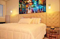 Para o quarto do apartamento na praia, o casal queria um ambiente aconchegante. Quem foi chamado para o trabalho foi o designer de interiores Alexsandro Araujo. O quarto, de 16,2 m², conta com uma cabeceira feita de placas de MDP cobertas com espuma e capitonê de seda indiana.