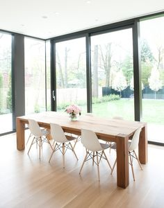 Wood table, white eames chairs. Love table/chairs or family friendly kitchen dining. Also love how it is positioned in window nook.