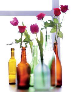 Pequenas rosas e tulipas decoram garrafas de diferentes formas e cores, na produção de Camile Comandini. A ideia fica simples, mas muito bonita