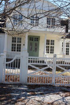 Vitt hus. Spröjsade fönster. Grön pardörr. Grind. Staket.