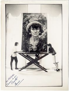 Marion Pike and Coco Chanel leaning on the artist's portrait of the designer.
