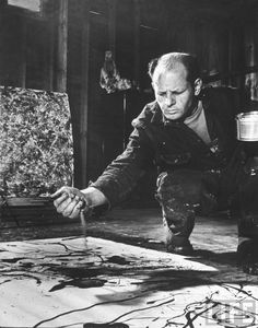 Martha Holmes | Portrait of Jackson Pollock |  Artist Jackson Pollock dribbling sand on painting while working in his studio. | Location: Springs, NY, US | Date taken: April 1949  Photographer: