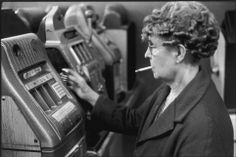 In Brixton, South London, an elderly woman pumps coins into a one-armed bandit in an amusement arcade while smoking a cigarette, oblivious to the photographer standing a few feet away (1960s).