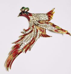 A fabulous vintage Corocraft figural! It is a very large bird, possibly a phoenix or a bird of paradise. It is sterling silver with a gold wash, red,