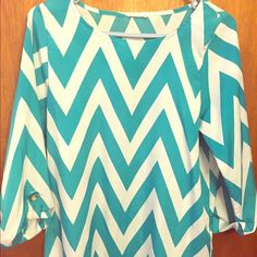 Boutique Chevron Blouse Turquoise and white chevron patterned blouse.  Gold button detail on cuffs.  Three quarters sleeves.  Hits at hip. Tops Blouses