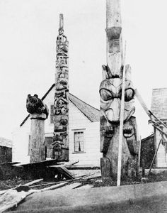 Property House with its frontal pole. The pole on the left with the horizontal bear on top is a mortuary pole, and the pole on the right is a memorial pole. Note the copper attached to the memorial pole above the head of the standing bear.